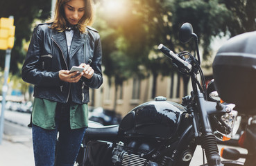 Fotomurales - Girl in leather jacket holding smart phone on background motorcycle in sun flare atmospheric city, hipster using in female hands and texting mobile, motorbike street lifestyle, tourist planing route