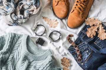 Flat lay women's clothing for autumn walks, top view. Brown suede boots, jeans, a blue pullover, scarf, bracelets, watches, headphones, perfume on a light background. Fashion concept Wall mural