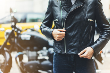 Girl unfastens black leather jacket on background motorcycle taxi in sun flare atmospheric city, hipster biker female hands closeup, motorbike street lifestyle, traveler concept