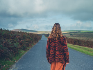 Young woman standing in the road on moor