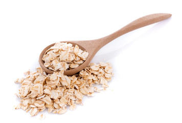 Oat flakes pile in wooden spoon on white background
