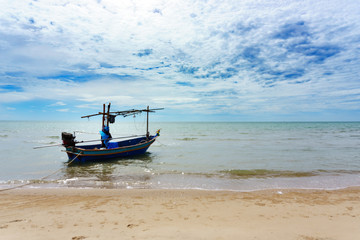 small local thai fishing boat parking or floating on the sea at the beach with blue sky and cloud in sunny day.