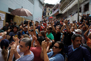 Supporters of Carlos Ocariz, candidate for the Venezuelan coalition of opposition parties (MUD), cheer him on as he arrives at a polling station to cast his vote during a nationwide election for new governors in Caracas