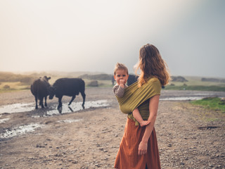 Mother with baby in sling looking at cows