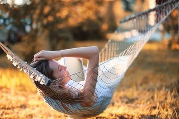 Beautiful girl in hammock reading a book