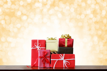 Christmas holidays and Happy New Year background. Gift boxes on wooden table front of yellow bokeh background.