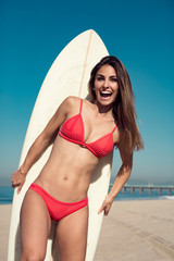 young woman standing with a surfboard at the beach.