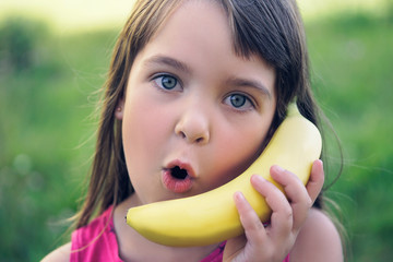 The girl tries to speak by means of a banana instead of phone