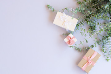Green leaves with gift boxes on blue background from above with copy space, flat lay scene
