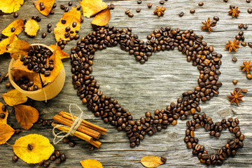 a heart of coffee beans strewn with autumn yellow leaves, anise and cinnamon on a wooden surface.