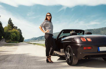 Fashionable young woman stahds near the cabriolet car