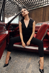 beautiful girl with dark hair in elegant clothes posing in luxurious car