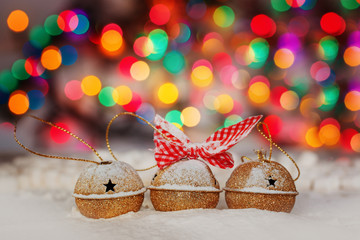 Greeting Christmas Card with Gold Jingle Bells on Colorful Bokeh Background.