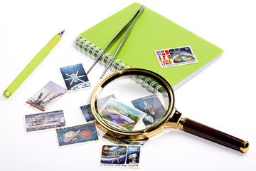 Collection of postage stamps with a magnifying glass and a notebook with a pen.