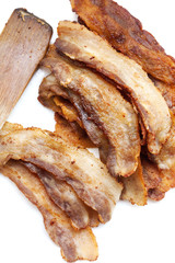 Fried pork bacon and wooden spatula on a white background