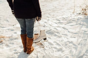 Rear view of a woman carrying ice skates against snowy background