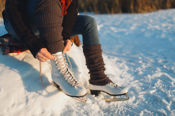 Cropped image of a woman putting ice skates on. Woman lacing ice skates at the edge of a frozen lake.
