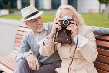 Two pensioners sit on a bench and take photos on an old film camera. They are smiling