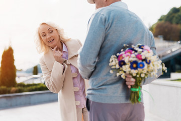 An elderly man is holding a bouquet of flowers behind back. A woman came on a date and tries to spy on what hides a man