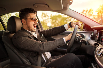 Angry business man driving and honking