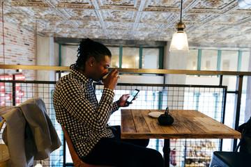 Man drinking tea and using phone