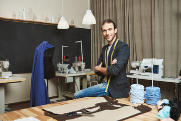 Artist and his work place. Portrait of mature attractive caucasian male clothes designer with stylish hairstyle and fashionable outfit sitting in his studio, posing for photo in fashion magazine.