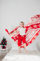 Boy jumping on the bed covered with a blanket