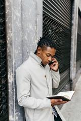 Black businessman talking phone at street