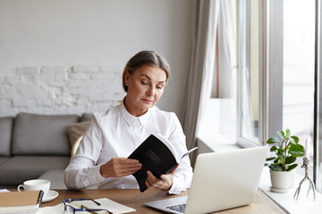 Indoor shot of serious concentrated middle aged female literary critic sitting in front of open laptop at her desk and looking through book in her hands, working on review, analysis and interpretation