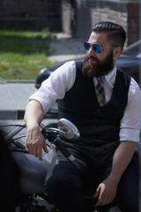Bearded Biker Man in black jacket sitting on motorbike outdoors
