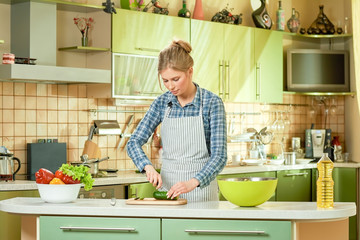 Woman cutting cucumber. Young female in the kitchen. Smart cooking tips.