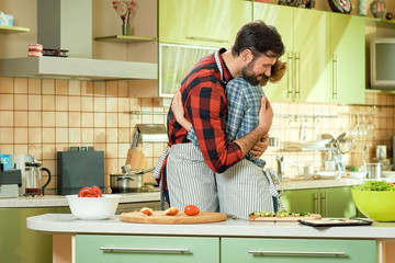 Couple hugging in the kitchen. Man and woman, cooking.