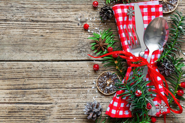 Christmas table place setting with christmas pine branches,ribbon, dried oranges and cones
