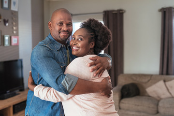 Affectionate African couple smiling and hugging each other at home