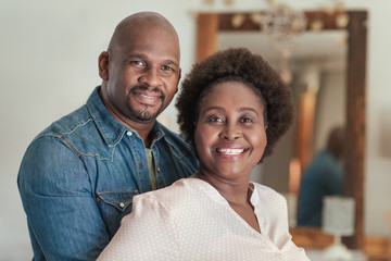 Content African couple smiling while standing together at home