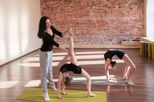Ballerinas rehearsal. Teenage sport life. Girls rhythmic gymnastics in dance class with female coach. Gym background, healthy lifestyle, workout concept