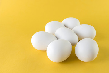 Seven white hen eggs isolated on yellow background