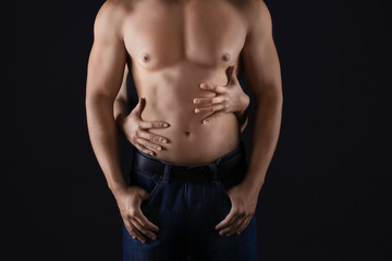 Female hands touching body of sporty young man on dark background