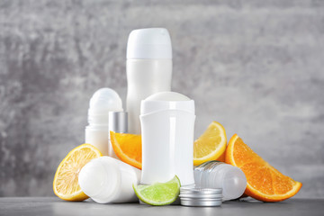 Deodorants for women and citrus fruits on table