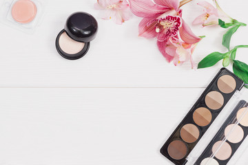 Decorative flat lay composition with makeup products, cosmetics and flowers. Flat lay, top view on wooden background.