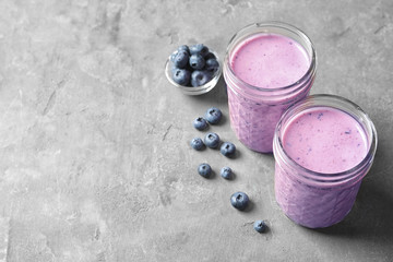 Jars with berry protein shakes on table