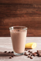 Glass with chocolate protein shake on wooden table