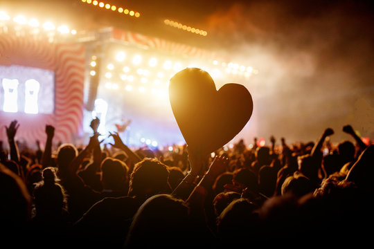 Close up a heart among the crowd of people at during a live concert