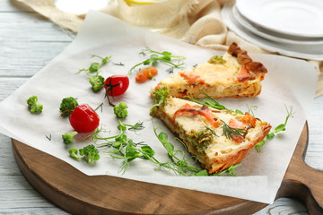 Board with pieces of salmon quiche pie on table