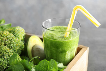 Glass with green smoothie and products in wooden basket on grey background