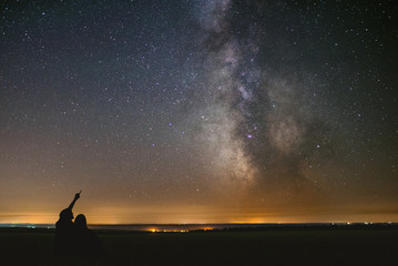 couple in love under stars of center our home galaxy Milky Way. Two people at night under stars