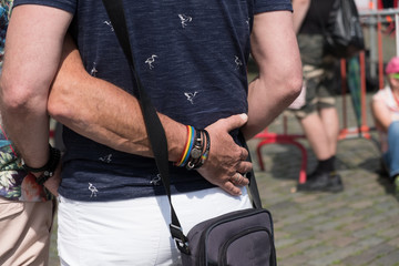 Homosexual couple stand with arms around each other attending gay pride even outside in the Grote Markt in Antwerp. Gay couple in love enjoying a summer afternoon outside.