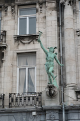 Statue of the Greek God Hermes (or Roman God Mercury) holding a caduceus, arm raised to the heavens on the side of a building in Antwerp, Belgium.