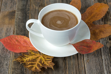 swirling cream and coffee in white cup on autumn leaves and rustic wood