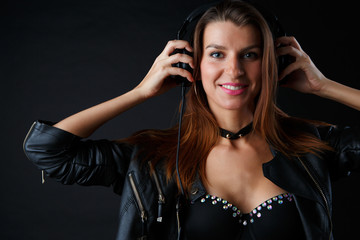 Photo of young woman wearing headphones in leather jacket